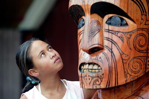Niña maorí observando una figura tallada en madera en Nueva Zelanda