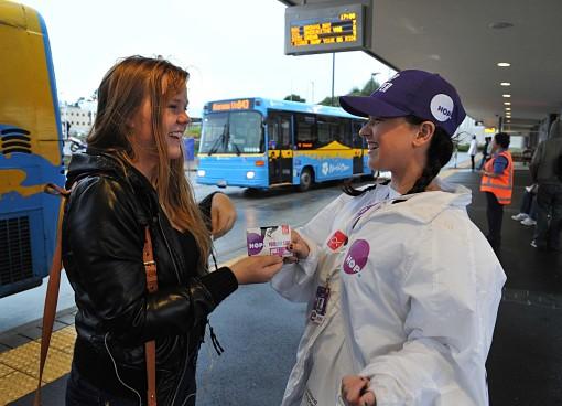 Joven entregando tarjeta HOP en una promoción de Auckland